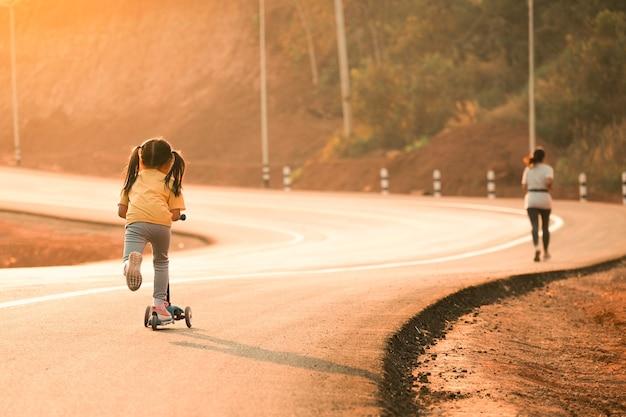 일몰 빛 시간 시골 도로에서 롤러 스케이트 보드와 함께 조깅하는 엄마와 아이 소녀