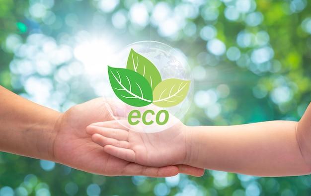 흐릿한 녹색 자연 배경에 어린 식물과 에코 아이콘을 들고 있는 엄마와 아이의 손