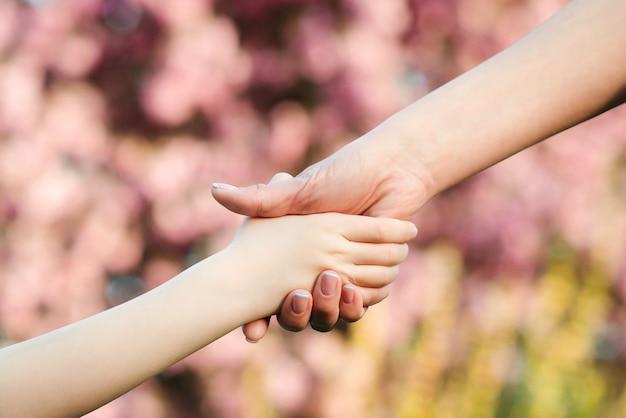 母と子は自然の背景を手渡します。家族のサポート、助け、そして信頼。