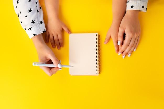 母と子の手がメモ帳、トップビューで書く