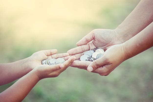 Мать и ребенок, держащая монету в руках, как концепция экономии денег в старинном цветовом тоне