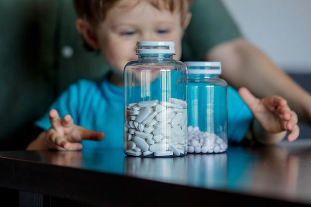 Мать и ребенок, держа две банки таблеток
