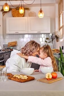 엄마와 아이 포옹, 함께 아침 식사를 즐기고. 아침에 웃고, 웃고, 말하고, 친절한 엄마와 딸