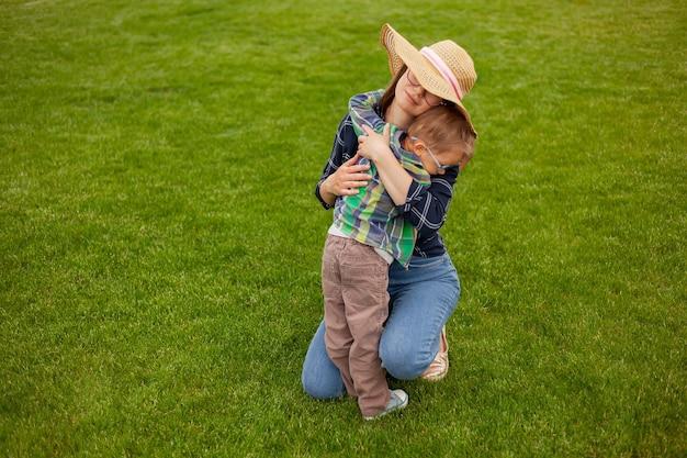 뒤뜰의 잔디밭에 앉아 포옹하는 엄마와 아이