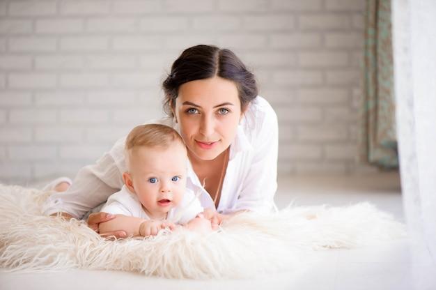 Мать и ребенок в белой комнате. мама и малыш в подгузнике