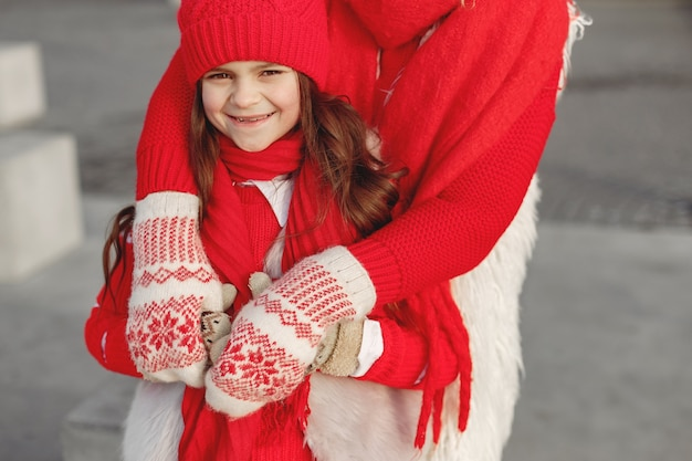 엄마와 가족 크리스마스 휴가에 니트 겨울 모자에 아이. 엄마와 아이를위한 수제 양모 모자와 스카프. 아이들을위한 뜨개질. 니트 겉옷. 여자와 공원에서 어린 소녀입니다.