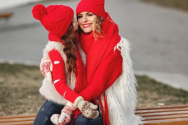 家族のクリスマス休暇にニットの冬の帽子をかぶった母と子。ママと子供のための手作りのウールの帽子とスカーフ。子供のための編み物。ニットアウター。公園の女性と少女。