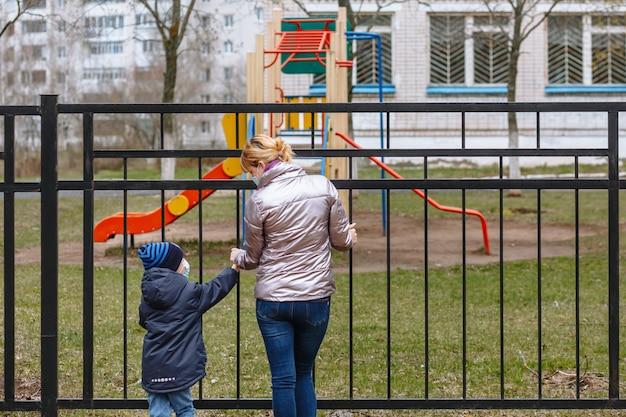 Мать и ребенок в медицинских масках смотрят друг на друга