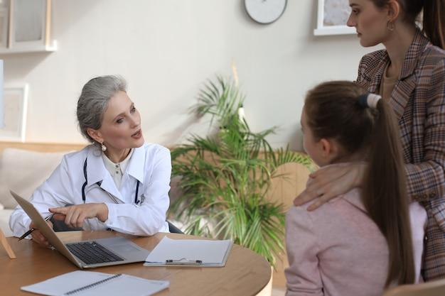 의사 사무실에서 소아과 의사를 만나는 엄마와 아이는 병원 책상에 앉아 있습니다.