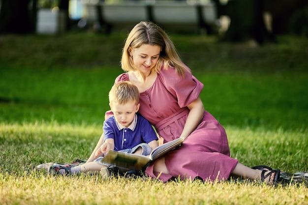 母と子は草の上に横たわって、屋外で本を読みます