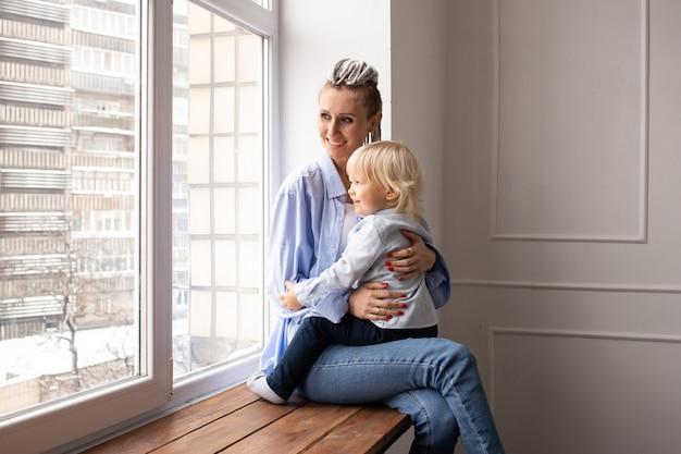 격리 시간에 창문을 통해 보는 엄마와 아이