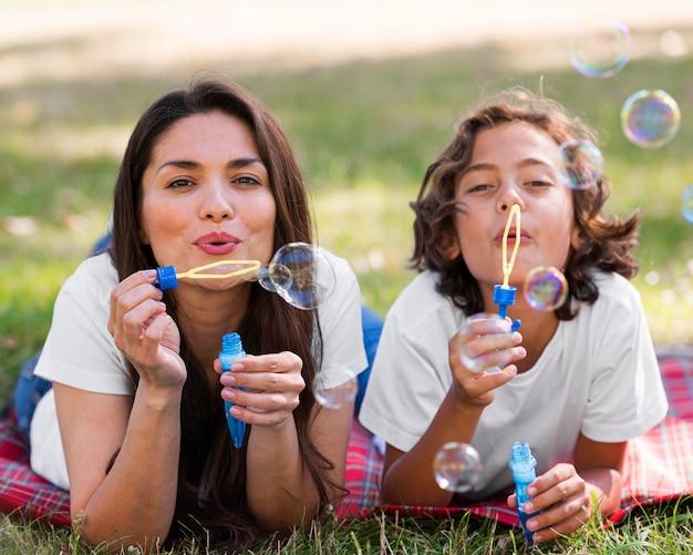 母と子が一緒に屋外で風船を作る