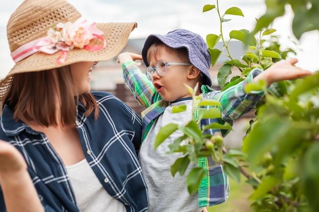 나무 근처에 있는 엄마와 아이, 뒤뜰 정원에서 정원 가꾸기