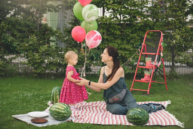 Мать и дитя на пикнике едят большие арбузы. летняя семейная вечеринка на открытом воздухе с малышкой