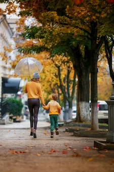 Мать и дитя на улице под зонтиком гуляют в дождливую погоду