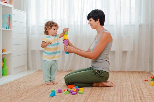 엄마와 아이가 보육원에서 바닥에서 놀아요. 엄마와 어린 소년이 색깔의 블록 탑을 짓고 있습니다.