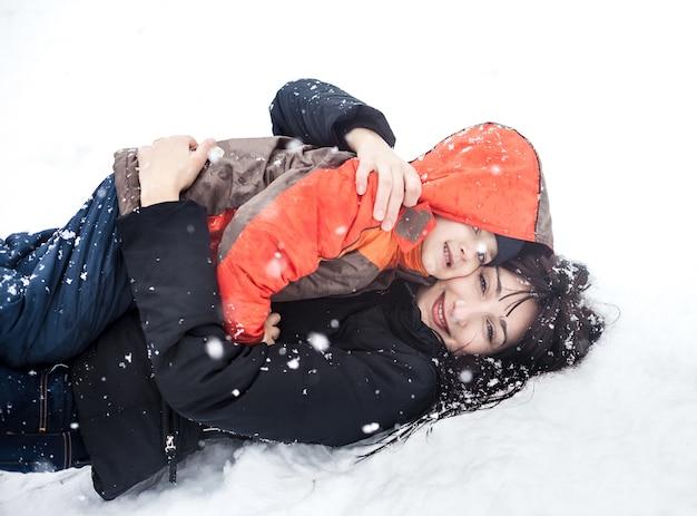 Мать и ребенок играют в снегу