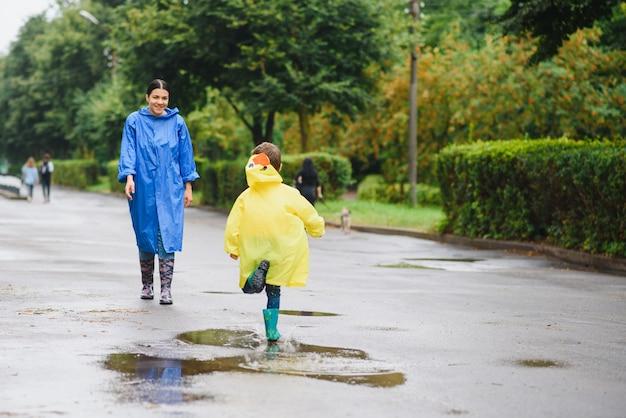 Мать и ребенок играют под дождем, в сапогах и плащах