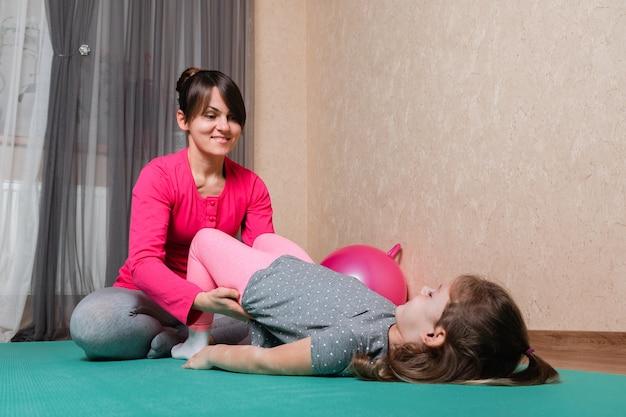 Мать и дитя занимаются спортом в доме. домашнее здравоохранение