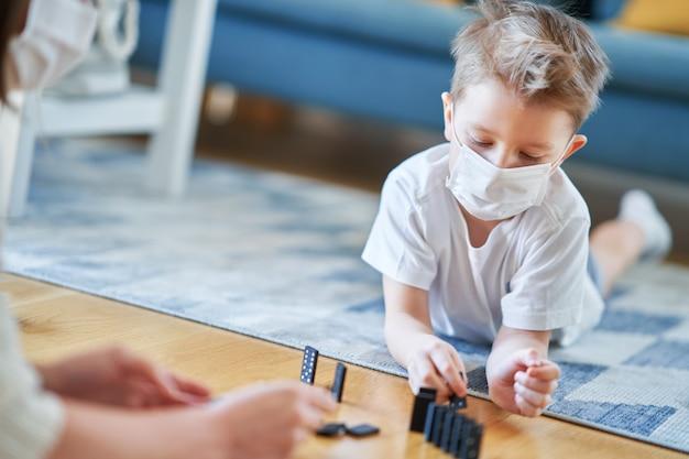 コロナウイルスのパンデミックの間に家の隔離で一緒に遊ぶ母と子