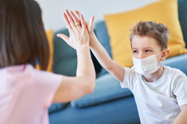 コロナウイルスのパンデミック時に自宅隔離で一緒に遊ぶ母と子