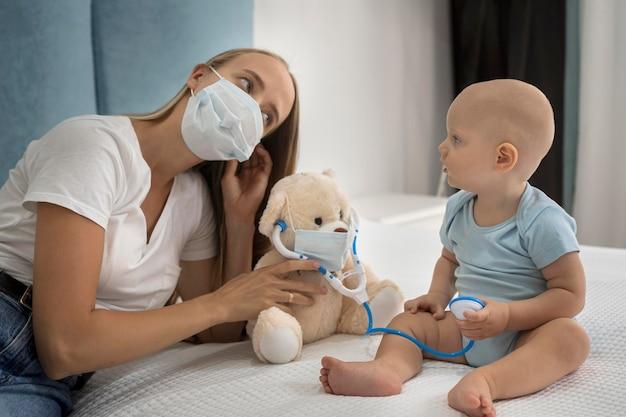 Мать и ребенок играют с плюшевым мишкой с медицинской маской