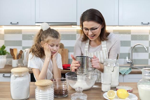 엄마와 아이가 함께 집 부엌에서 빵집을 준비. 여자는 밀가루를 체로 치고, 어린 딸에게 컵 케이크 요리하는 법을 가르칩니다.