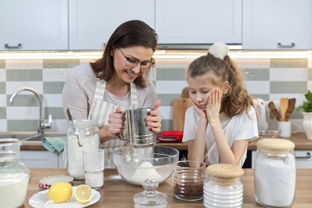 母と子が家庭の台所で一緒にパン屋を準備します