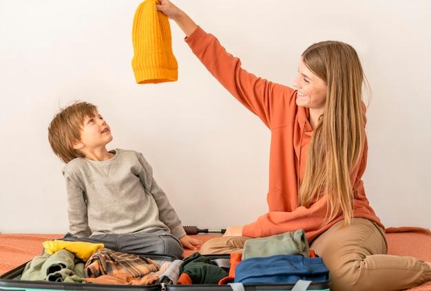 Мать и дитя готовят багаж к поездке