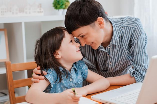 Мать и дитя школьница дома на ноутбуке, выполняя домашнее задание в школе в период пандемии и коронавируса