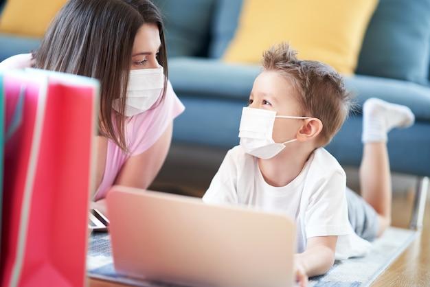 Мать и ребенок делают покупки в интернете во время пандемии коронавируса