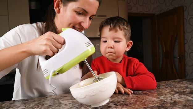 Мать и дитя размешивают тесто миксером