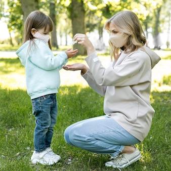 Мать и ребенок, используя дезинфицирующее средство для рук
