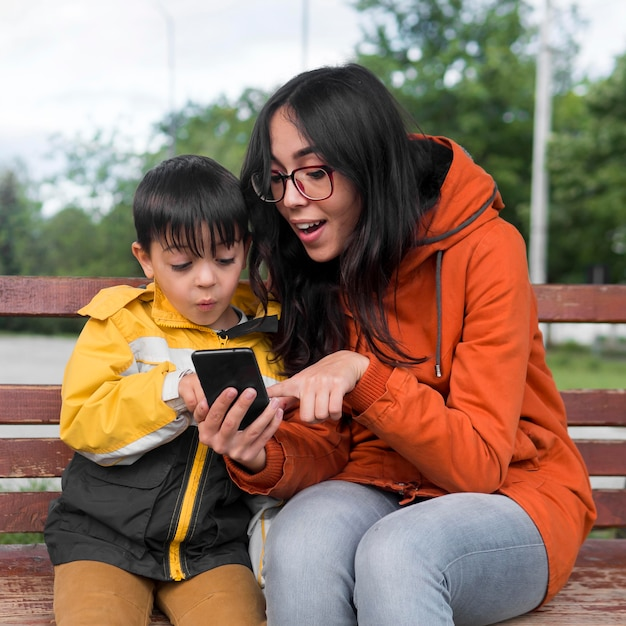 Мать и дитя с помощью мобильного телефона