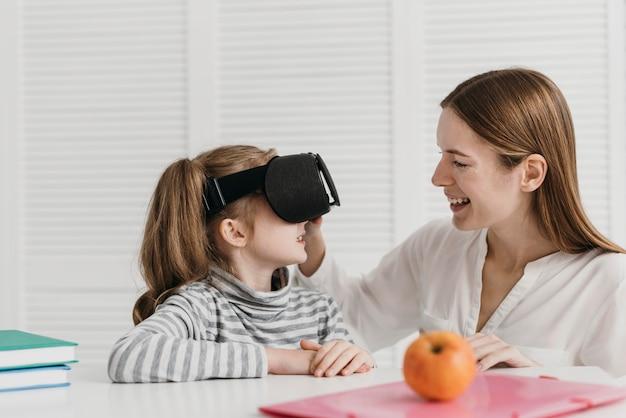 Мать и ребенок с помощью гарнитуры виртуальной реальности и счастливы