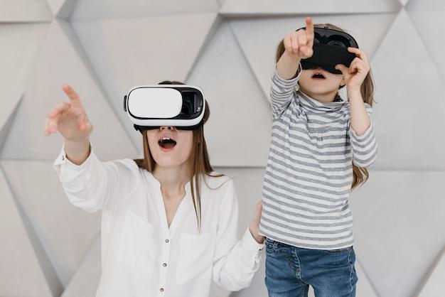Мать и ребенок, используя вид спереди гарнитуры виртуальной реальности