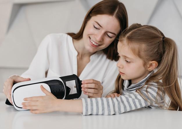실내에서 가상 현실 헤드셋을 사용하는 엄마와 아이