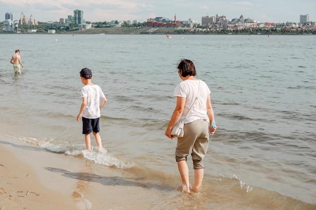 砂浜を歩く母と子。海の冷たい水。裸足でビーチに沿って歩きます。暑い夏は涼しくなります。足元の小さな波 Premium写真