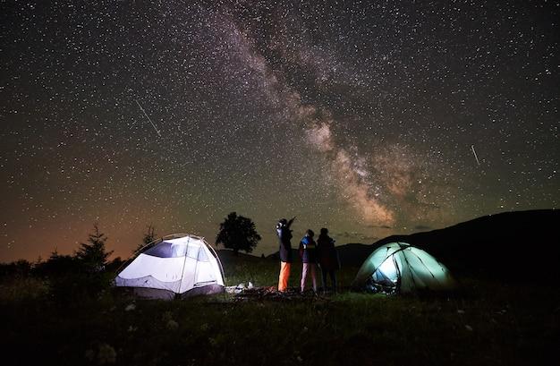 어머니와 밤에 캠핑하는 어린이