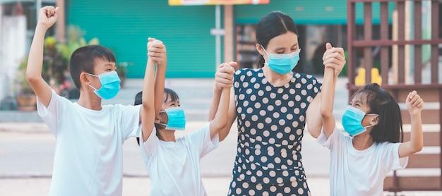 コロナウイルスを保護するために子供にマスクを着用する母と子の家族