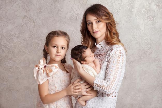 Мать и дети, новорожденная и старшая сестра. концепция любви, доверия и нежности