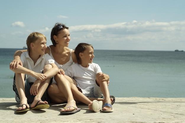 Мать и дети на фоне моря