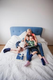 어머니와 아이들은 침대에서 책을 읽고