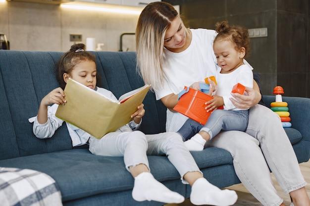 Мать и дети отдыхают вместе на диване у себя дома в гостиной. маленькие девочки читают книгу и играют в игрушки.