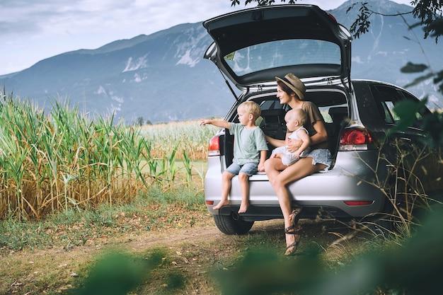 開いた車のトランクに座って、ロードトリップで自然家族を見ている母と子