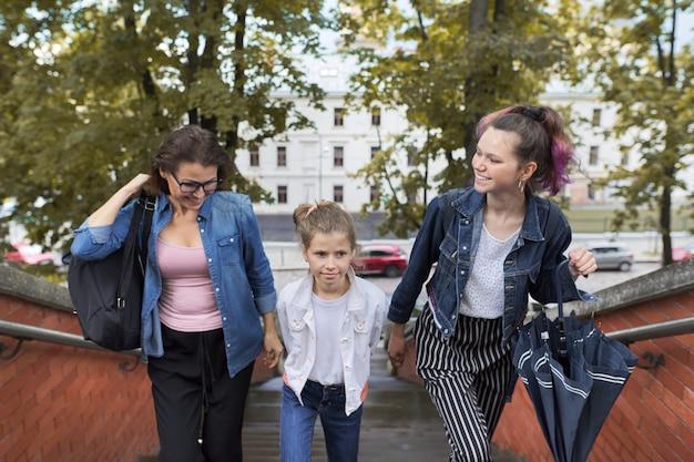 Мать и дети две дочери, идущие по лестнице