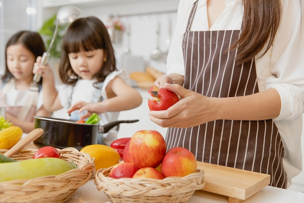 野菜や果物から家庭の台所で健康的な食品を準備することに満足している母と子