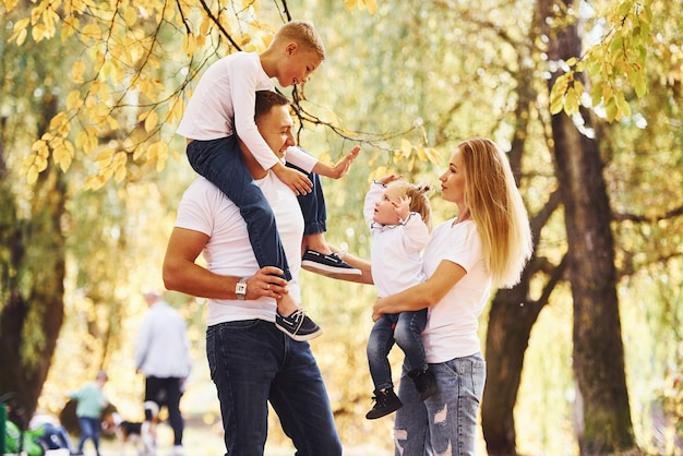 엄마와 아빠는 아이들을 어깨와 손에 안고 있습니다. 쾌활한 젊은 가족이 함께 가을 공원에서 산책을 합니다.