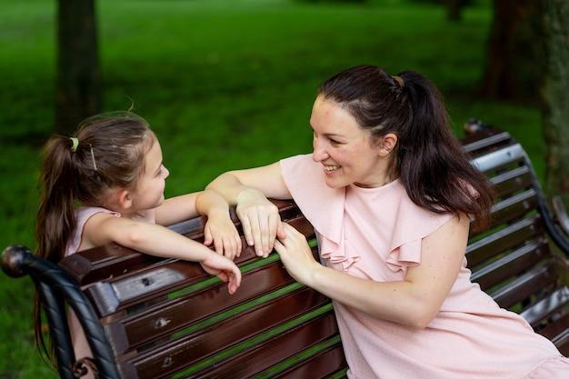 Мать и дочь 5-6 лет гуляют в парке летом, мать разговаривает с дочерью, сидя на скамейке