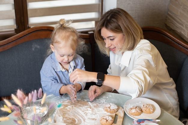 Мать и дочь готовят печенье и веселятся на кухне.